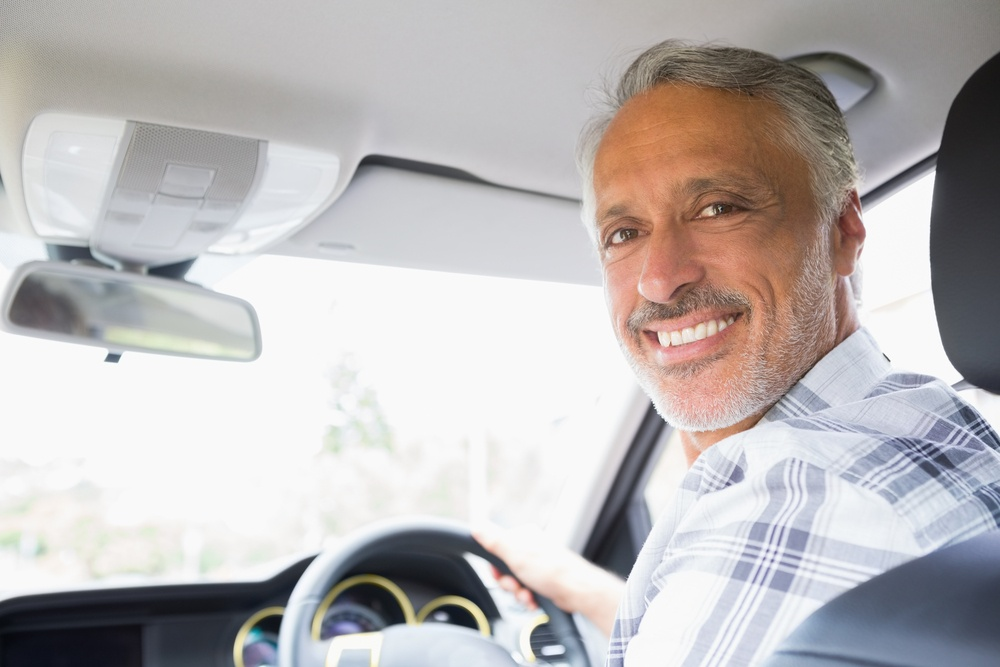 Man smiling while driving in his car