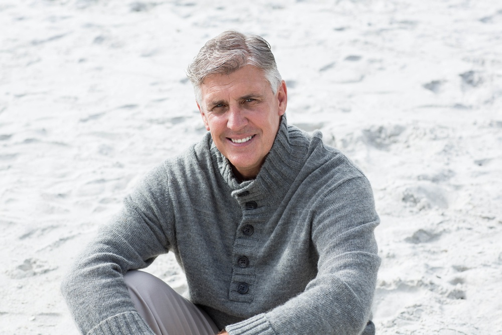 Smiling man sitting down in the sand at the beach