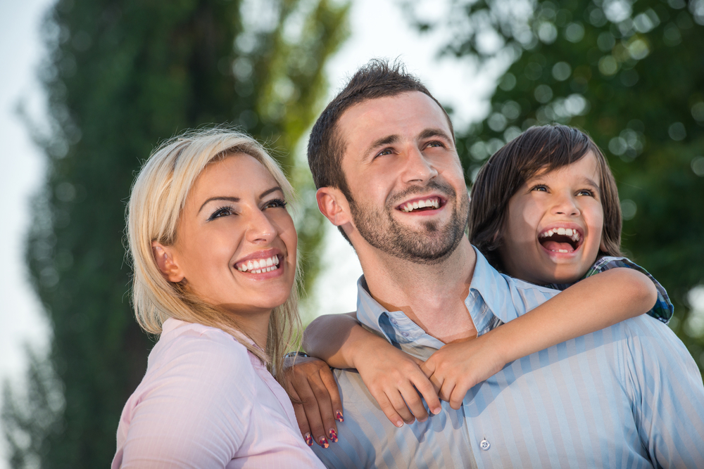 Smiling parents with kid outdoors looking up